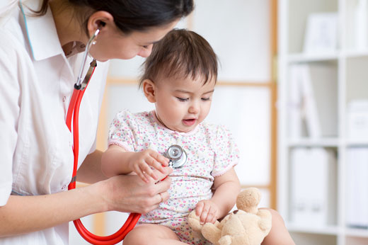 A nurse using a stethoscope on a baby.