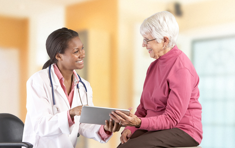 A doctor explaining information to patient using a tablet