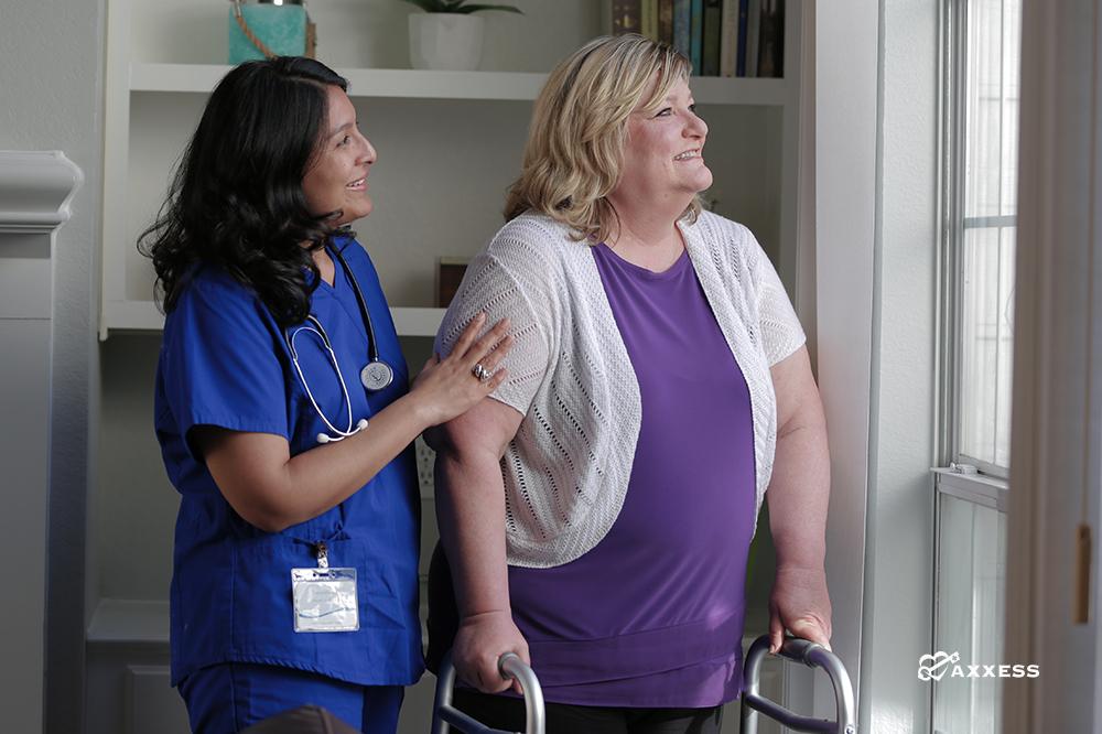 Nurse helping patient on a walker