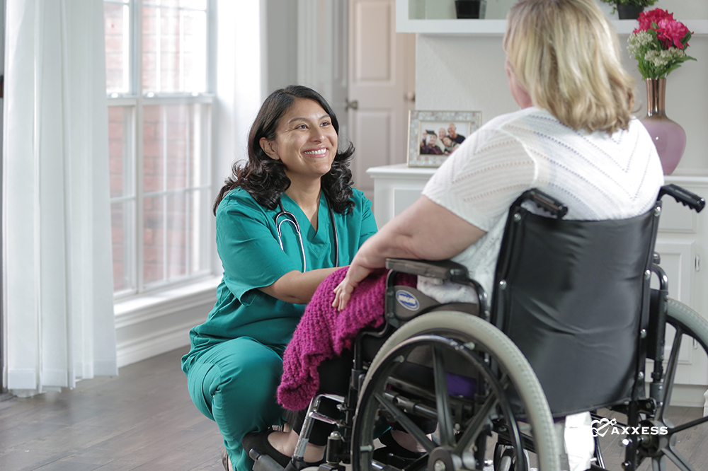 A nurse kneeling in front of a patient sitting a wheelchair.