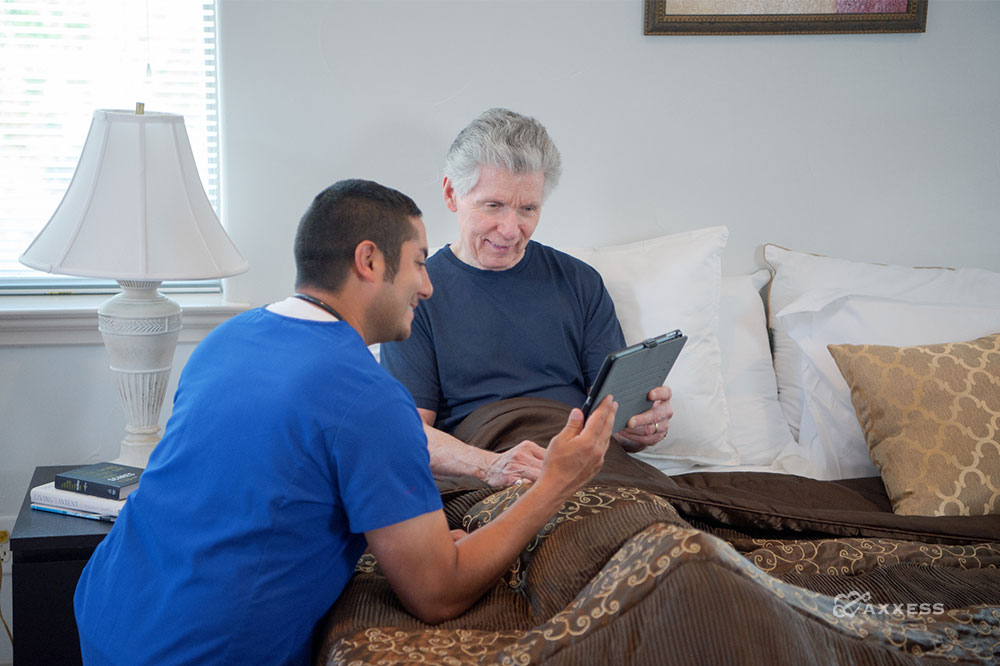 a clinician showing a tablet to a patient in bed
